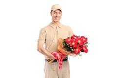 Een leveringsmens die een bos van bloemen levert Royalty-vrije Stock Afbeelding