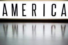 Een licht op raad toont de uitdrukking AMERIKA Stock Foto