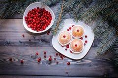 Een lichte houten lijstbovenkant met een plaat van vers gebakken die muffins met rode die bessen worden verfraaid met wit poeder  stock fotografie
