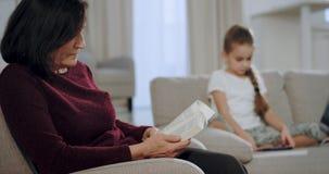 In een lichtgevende en ruime woonkameroma die een interessant boek op de bank lezen terwijl haar nicht die op a spelen stock videobeelden