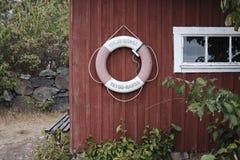 Een lifesaverring op een kleine hut in een bos stock afbeeldingen