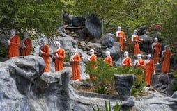 Een lijn van Boeddhistische monniksstandbeelden die de Gouden Tempel naderen in Dambulla, Sri Lanka royalty-vrije stock afbeelding