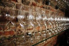 Een lijn van opgepoetste wijnglazen voor een bakstenen muur in een wijnbar stock foto's