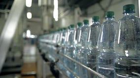 Een lijn voor het bottelen van mineraalwater in flessen stock videobeelden