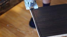 Een lijn wordt getrokken op het bord De mensenzagen met een elektrische figuurzaag op de lijn Het huiswerk met meubilair stock video
