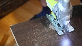 Een lijn wordt getrokken op het bord De mensenzagen met een elektrische figuurzaag op de lijn Het huiswerk met meubilair stock footage