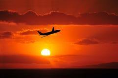 Lijnvliegtuig die in Tropische Zonsondergang vliegen stock foto