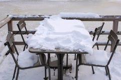 Een lijst en stoelen in de sneeuw Stock Fotografie