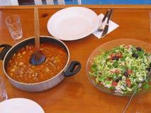 Een lijst met een plaat met gekleurde salade en een pot met een hutspot die aan open wordt voorbereid Turkije Stock Afbeelding