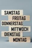 Een lijst van houten blokken die bovenop elkaar met een lijst van dagen van de zesdaagse het werkweek in het Duits, in de vertali stock afbeeldingen