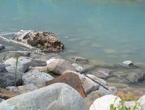 Een logboek en stenen in water van het meer Louise alberta canada royalty-vrije stock afbeelding