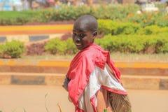 Een lokale jongen wandelt onderaan Kampala straat, draaien en glimlachen rond stock fotografie