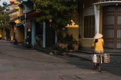 Een lokale Vietnamese Vrouw berijdt haar fiets om in hoi te werken stock afbeeldingen
