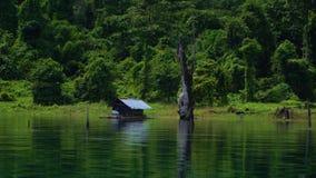 Een losgemaakt huis op de kust van het meer dichtbij de wildernis stock footage