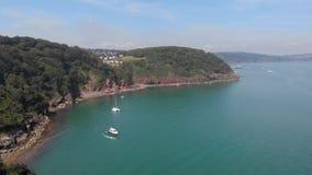 Een lucht achterwaartse lengte een baai hoopt Neus met ankerboot en turkoois water langs bosheuvel onder majestueus blauw s stock videobeelden
