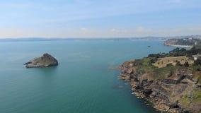 Een lucht achterwaartse lengte van een rotsachtige eilandrots Thatcher Point met vissersboot langs rotsachtige klip en turkoois w stock footage