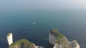 Een lucht achterwaartse vlieg over lengte van Oud Harry Rocks met kristal blauw water en boten onder een verbazende hazing blauwe stock footage