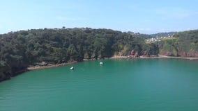 Een lucht voorwaartse lengte van een baai hoopt Neus met ankerboot en turkoois water langs bosheuvel onder een majestueus blauw stock videobeelden