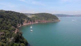 Een lucht voorwaartse lengte van een baai hoopt Neus met ankerboot en turkoois water langs bosheuvel onder een majestueus blauw stock footage