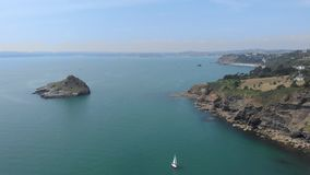 Een lucht voorwaartse lengte van een rotsachtige eilandrots Thatcher Point met het bewegen van boten langs rotsachtige klip en tu stock video