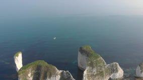 Een lucht voorwaartse vlieg over lengte van Oud Harry Rocks met kristal blauw water en boten onder een verbazende hazing blauwe h stock footage