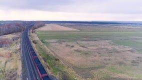 Een luchtcamera volgt een goederentrein in beweging met steenkool stock footage