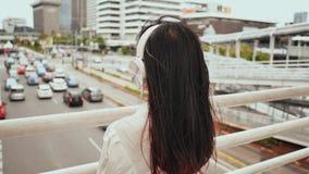 Een luistert de Aziatische meisjestribunes op een brug over verkeer en in witte hoofdtelefoons aan muziek stock video