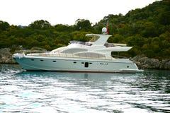 Een luxueus wit jacht bevindt zich in een baai op een eiland stock foto's