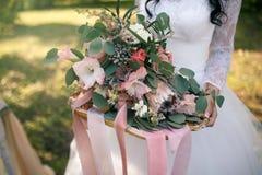 Een luxuriant huwelijksboeket van exotische bloemen op een gouden die dienblad met roze linten in de handen van de bruid wordt ve Royalty-vrije Stock Fotografie