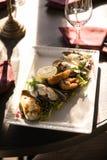 Een maaltijd van oesters met citroen en saus Plaat met mediterrane zwarte shell van de zeevruchtenschotel mosselen met kruiden stock afbeelding