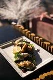 Een maaltijd van oesters met citroen en saus Plaat met mediterrane zwarte shell van de zeevruchtenschotel mosselen met kruiden stock foto