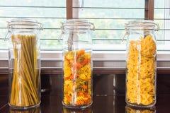 Een een Macaroni en Spaghetti van de verschilvorm in een glaskruik met Li royalty-vrije stock fotografie