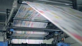 Een machine werkt, rollend gedrukte krant in typografiefaciliteit stock videobeelden