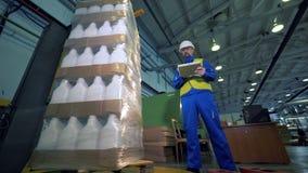 Een machine wrappes dozen terwijl een persoon die het werk, geautomatiseerde productie onderzoeken stock videobeelden