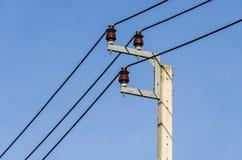 Een machtslijn en kabels op een blauwe hemel Stock Foto's