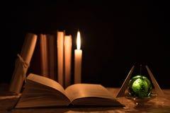 Een magische bal, een rol, een kaars en een oud boek in dark van de nacht Stock Fotografie