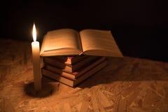 Een magische bal, een rol, een kaars en een oud boek in dark van de nacht Stock Foto's