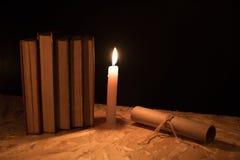 Een magische bal, een rol, een kaars en een oud boek in dark van de nacht Stock Foto