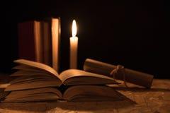 Een magische bal, een rol, een kaars en een oud boek in dark van de nacht Stock Afbeelding