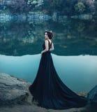 Een majestueuze dame, een donkere koningin, tribunes op de achtergrond van een rivier en rotsen, in een lange zwarte kleding Het  Stock Foto
