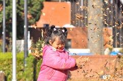 Een Maleis meisjesspel met droge bladeren Stock Afbeeldingen