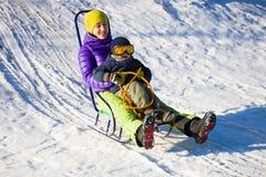 Een mamma met kind het sledding Stock Afbeeldingen