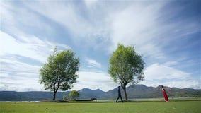 Een man die aan een vrouw in een rode kledingsvrouw lopen met een grote boom en een mooie hemelmening stock video