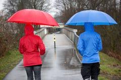 Een man en een vrouw lopen in de regen, gekleed met een regenjas Stock Foto