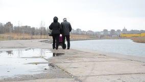 Een man en een vrouw met een wandelwagen stock videobeelden