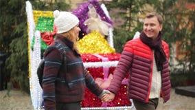 Een Man en een Vrouw zijn Holdingshanden en het Overgaan door de Santas-Slee met Colorfully Verpakte Giften op Kerstmismarkt A stock footage