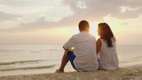 Een man en een vrouw zitten zij aan zij op het zand op het strand Samen bekijken zij de zonsondergang over het overzees stock videobeelden