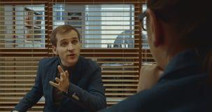 Een man en een vrouwen gaande onderhandelingen in het bureau bij de lijst stock video
