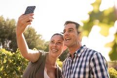 Een man en een vrouw die een selfie in de wijngaarden nemen Stock Afbeelding