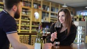 Een man en een vrouw drinken rode wijn in glazen, een restaurantbinnenland, drinken een jonge mens en een meisje wijn bij a stock video